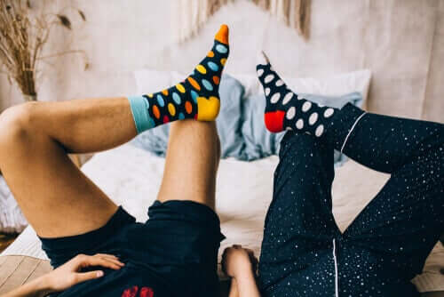 A couple wearing socks in bed.