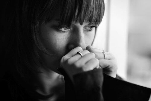 Woman with bangs staring out window glamorized suffering from depression