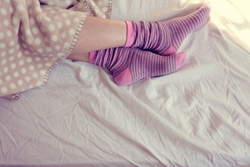 Person in bed with socks on