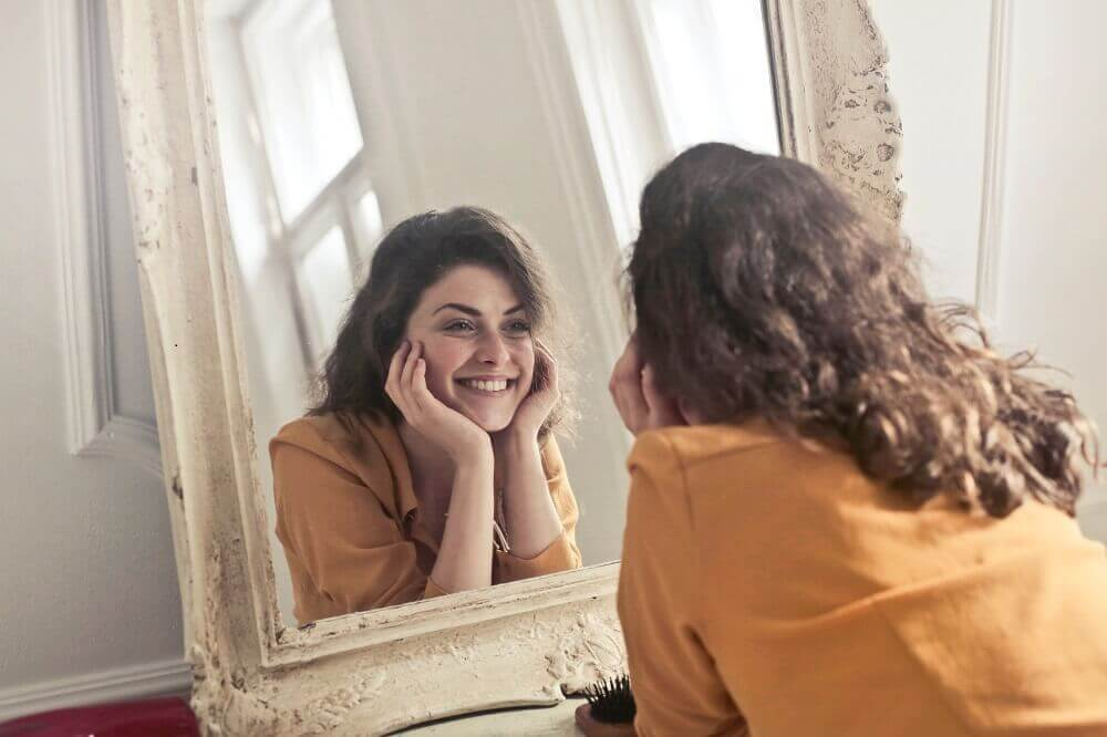 A woman smiling into the mirror.
