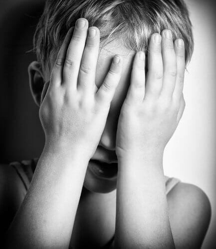 Lapsi peittää silmät käsillään