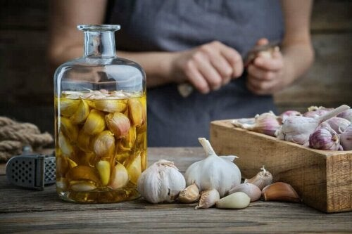 A person putting garlic in a jar with olive oil to help their vision loss.
