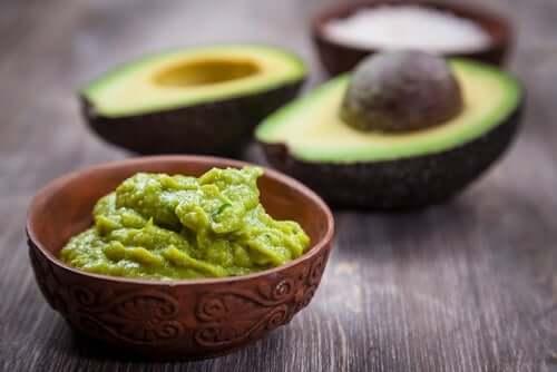 An avocado and a bowl of guacamole.