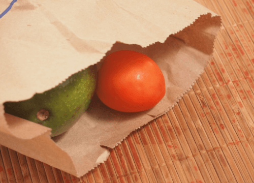 A couple pieces of fruit inside a paper bag.