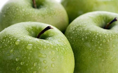 Some green apples with drops of water.