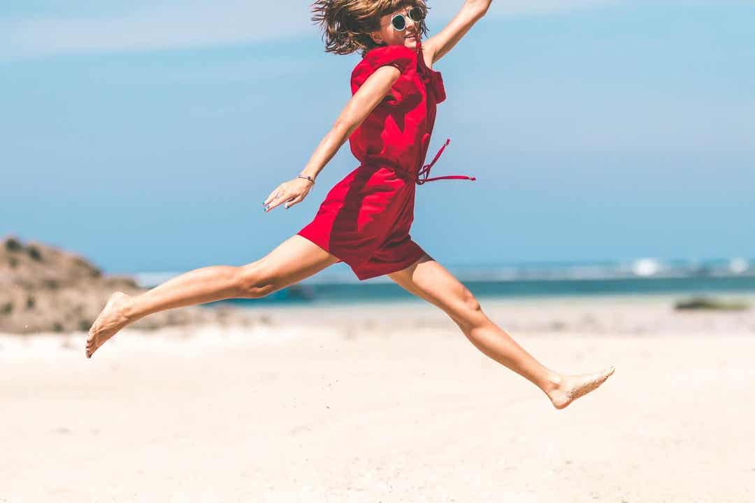 A woman leaping across the sand on the beach.