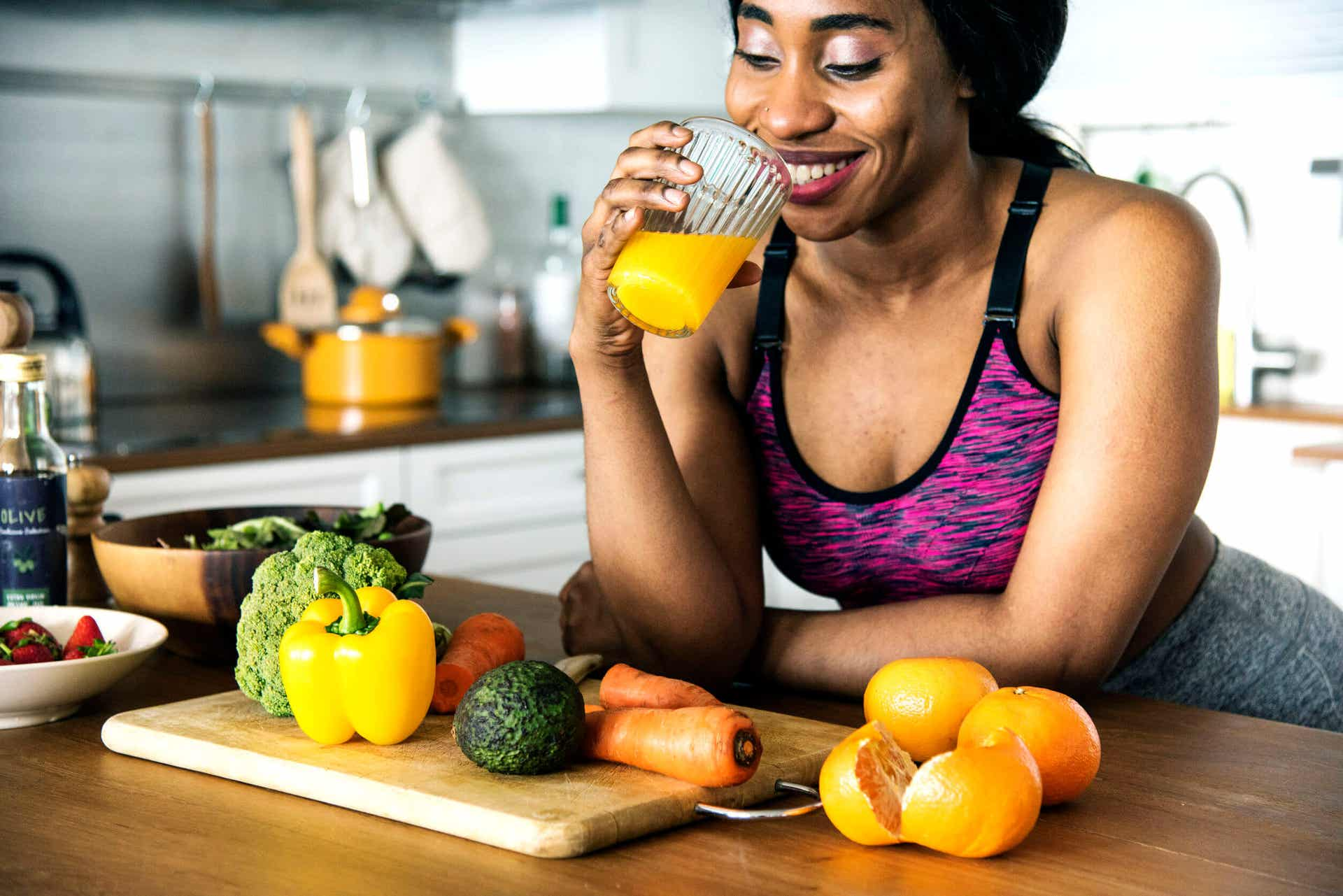 A woman in workout clothes drinking orange juice near a counter full of fruits and vegetables.