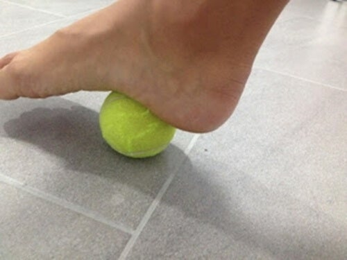 Person massaging pressure points in foot with a tennis ball