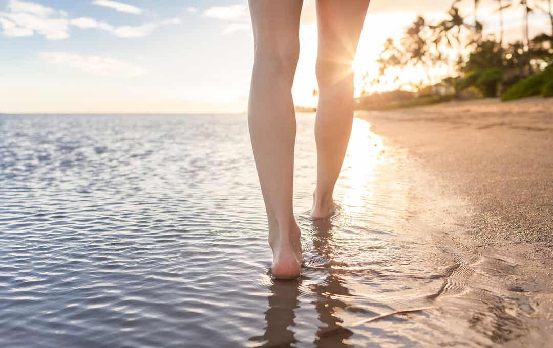 A woman walking along a tropical beach.