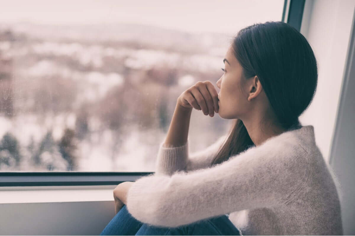 A woman gazing out the window at a wintery landscape.