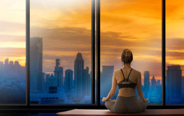 A woman meditating as she looks out at the city skyline.