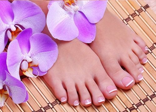 Feet on a bamboo mat with orchids on them.