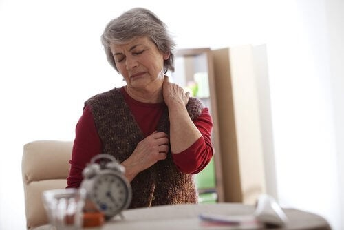 Elderly woman touching her neck to relieve neck pain.