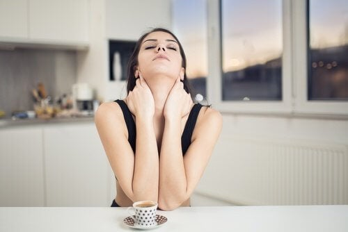 A woman at a kitchen counter drinking coffee and stretching her neck to relieve her neck pain.
