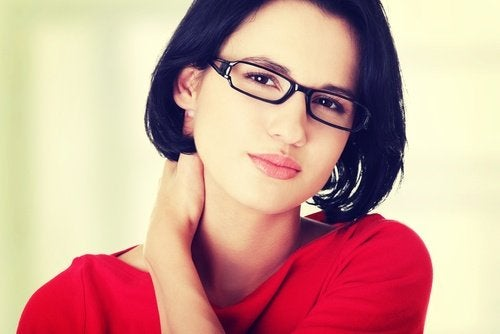 A wman in red with glasses touching her neck.