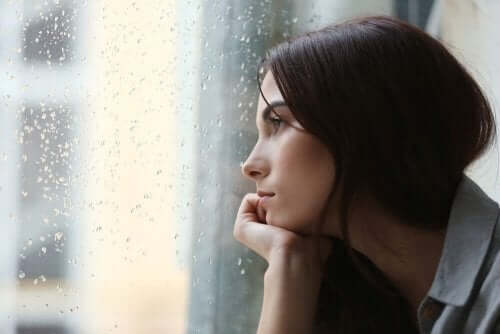 Woman looking out a window at the rain.
