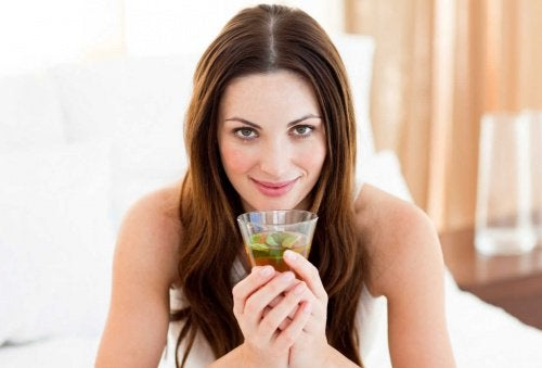 Woman drinking a glass of green tea lemonade