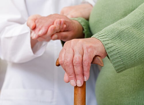 A doctor holding the hand of an elderly patient