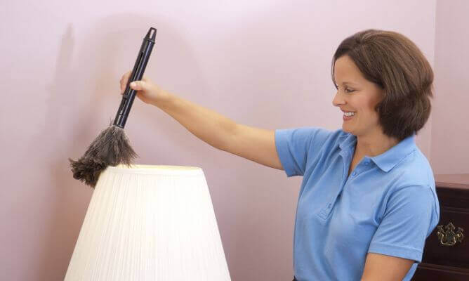 A woman cleaning a lamp.