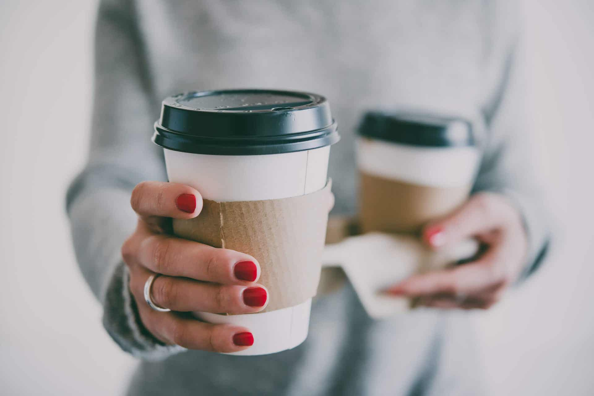 A woman holding two cups of coffee.
