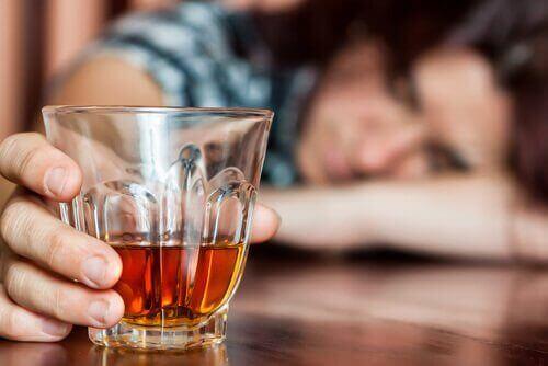 Glass of liquor on a table woman sleeping on bar