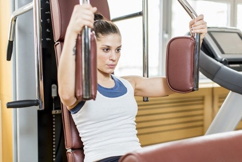 Woman in gym using weight machines to strength train healthy breasts