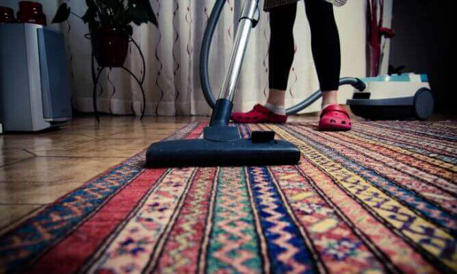 A person vacuuming a carpet.