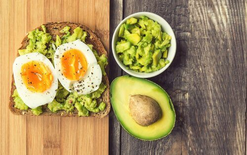 Bread with avocado spread and poached eggs on it.