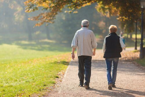 Couple walking on a path in autumn elderly couple strengthen your brain prevent dementia