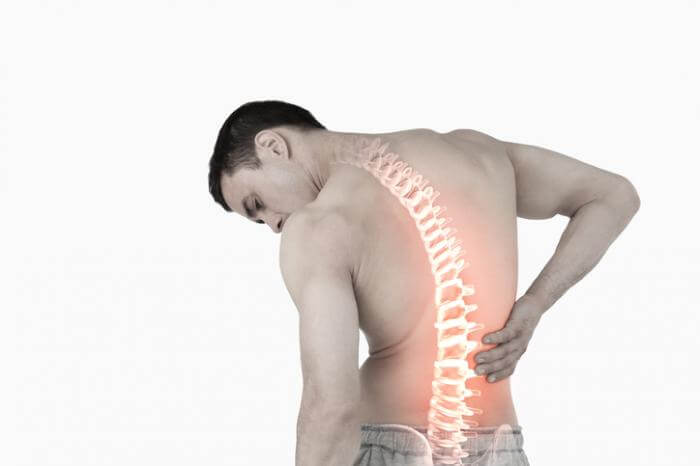 Man with visible spine holding his back