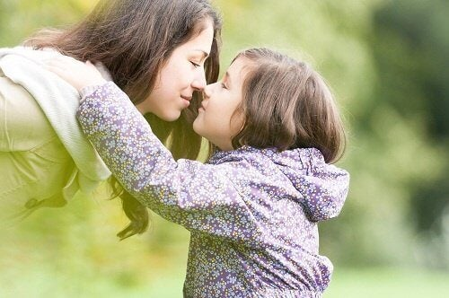 Mother kissing daughter parents love for children