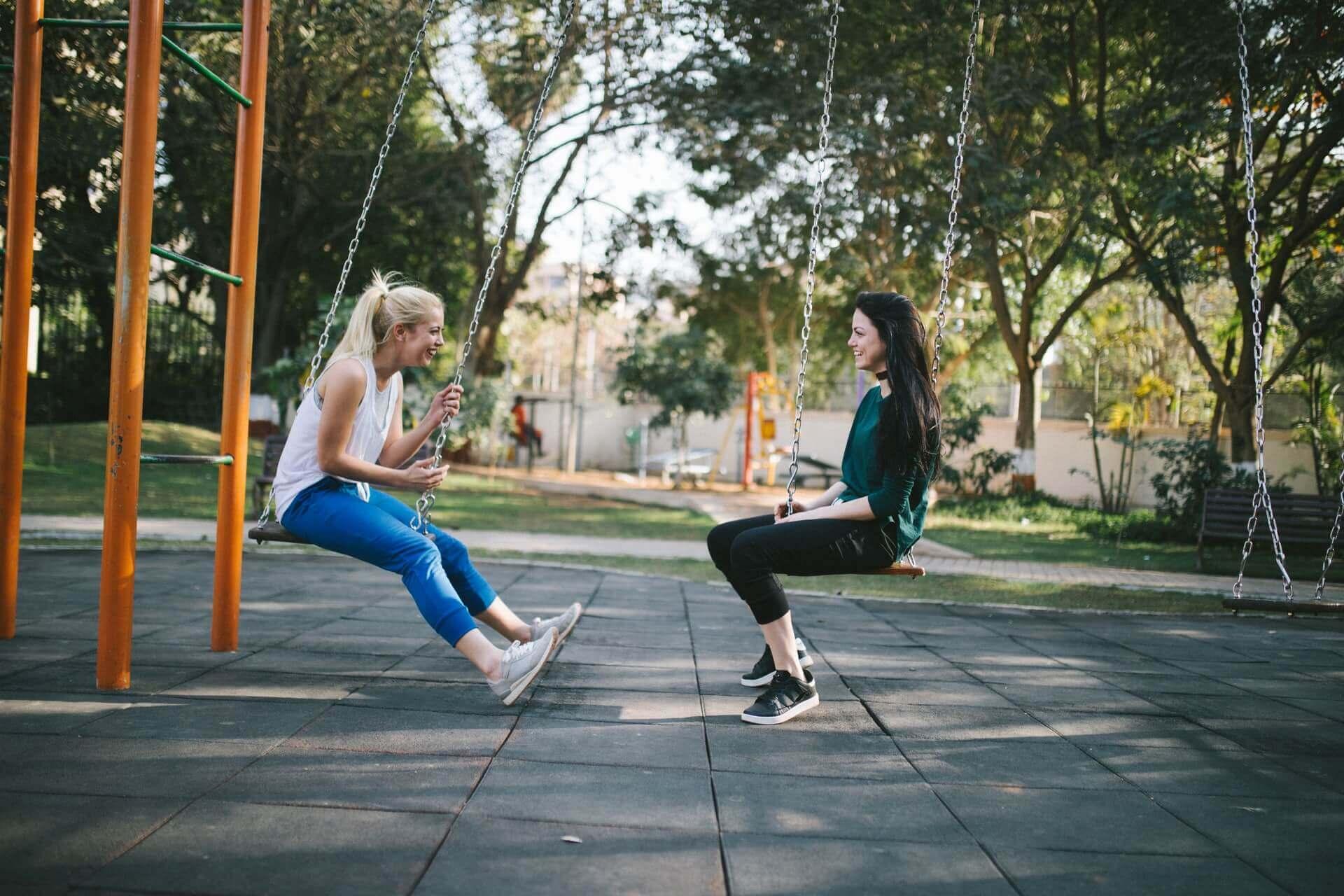 Two friends on swings.