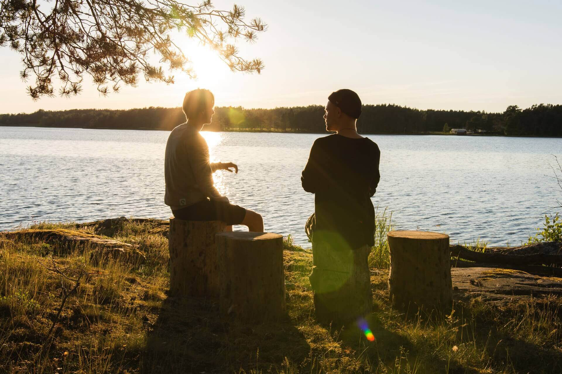 Friends talking by a lake at dusk.