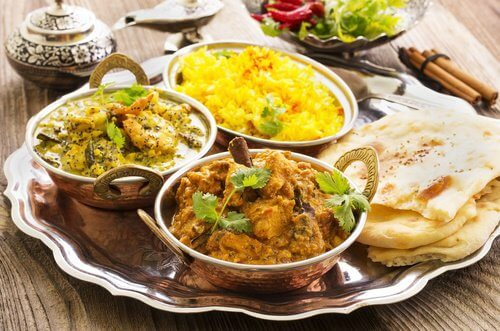 Different indian dishes on a silver platter.