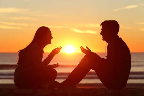 Two people laughing and talking on the beach at sunset.