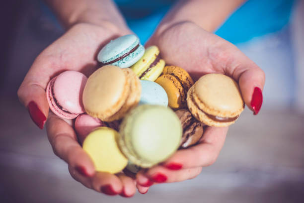 Girl-holding-colorful-French-macaroons-in-hands