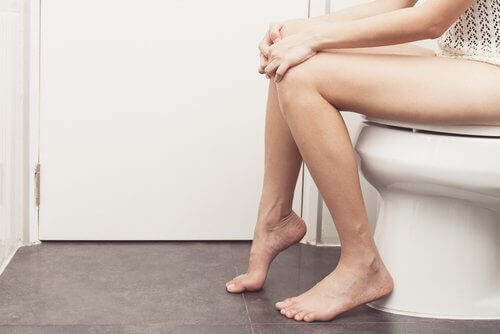 person sitting on toilet and experiencing anal itching, a symptom of anal cancer