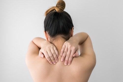 Woman touching her upper back with both hands uses for vicks vaporub