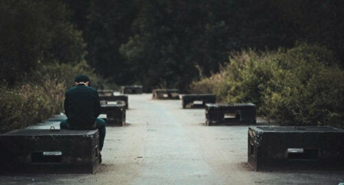 A man sadly sitting on a bench.