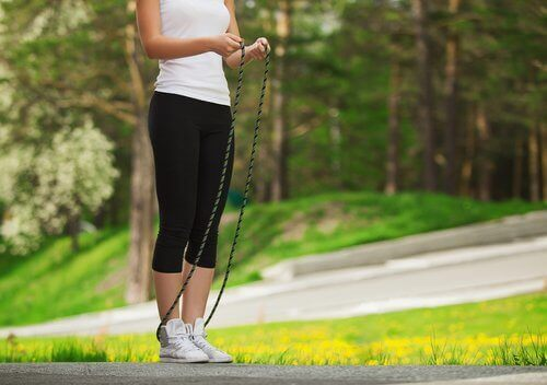 Woman outside in a park benefits of jumping rope
