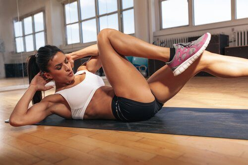 Woman on yoga mat doing cross crunches make time to work out