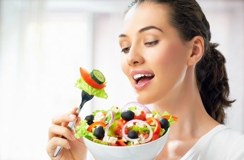 Woman eating a delicious salad work out and eat healthy diet