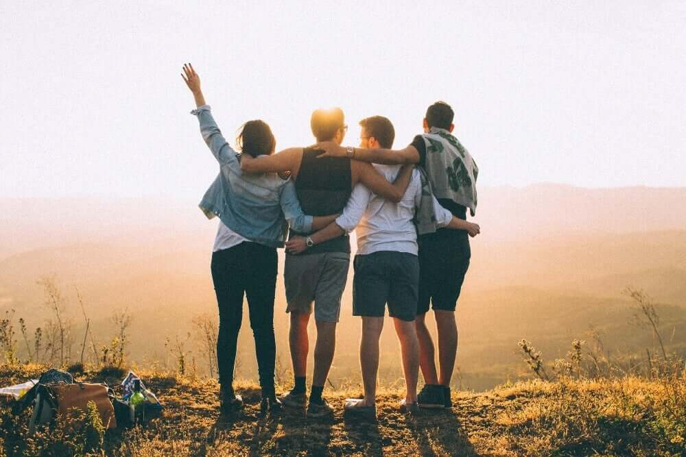 A group of friends with their arms around one another, looking out over a valley at dawn.
