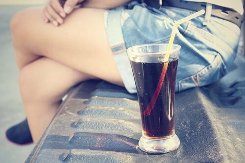 Woman's legs and glass of cola
