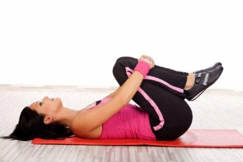 A woman doing knees-to-chest exercise.
