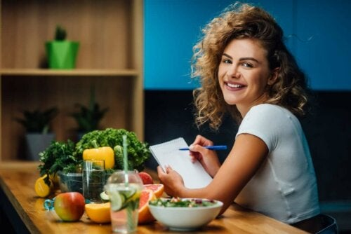 nutritionist sat at a table full of fresh fruit and veg creating a diet plan smiling at the camera