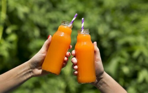 People holding bottles of carrot and ginger juice.