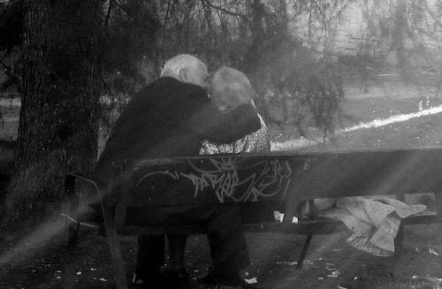 An elderly couple sitting in the park.
