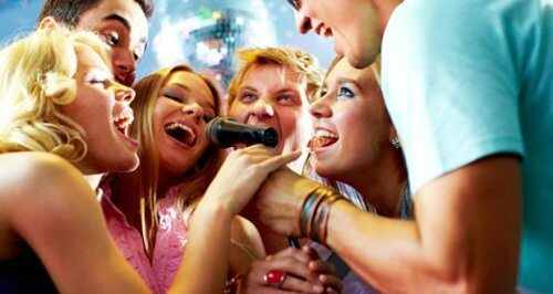 A group of people singing into a microphone.