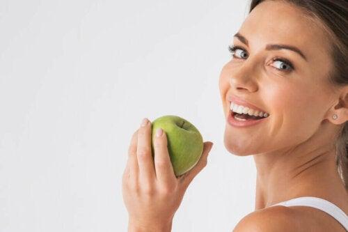 A woman holding an apple.